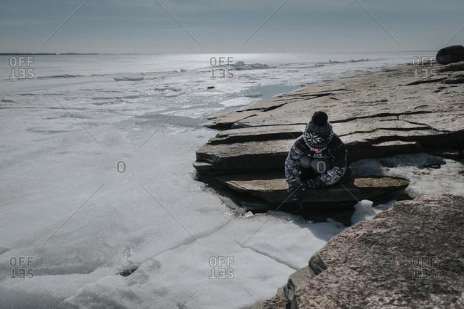 Boy sitting on rocks by frozen lake against sky