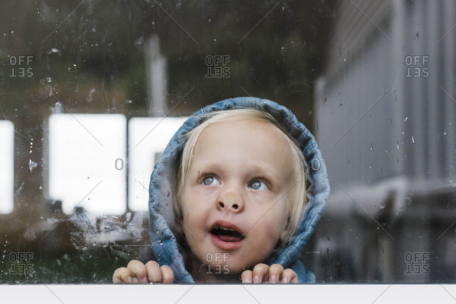 Close-up of girl looking through window seen through glass