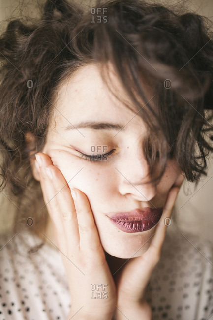 Close-up of woman with hand on chin puckering lips at home