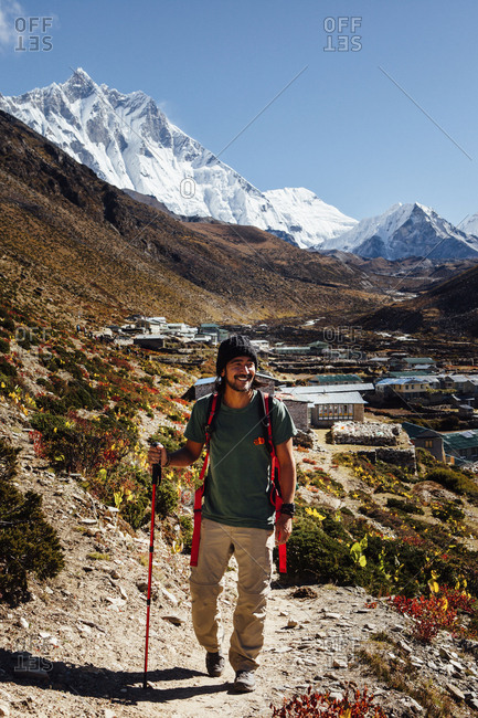 Male hiker with hiking pole walking on mountain against blue sky at Sagarmatha National Park