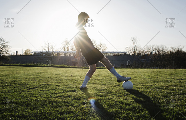 Man practicing soccer on grassy field against clear sky during sunset