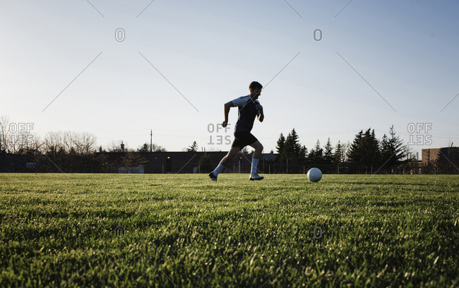 Man practicing soccer on grassy field against clear sky at park during sunset