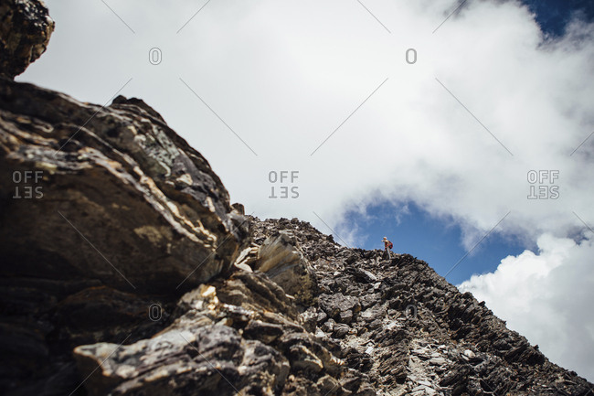 Mid distance view of hiker climbing mountain against cloudy sky during sunny day