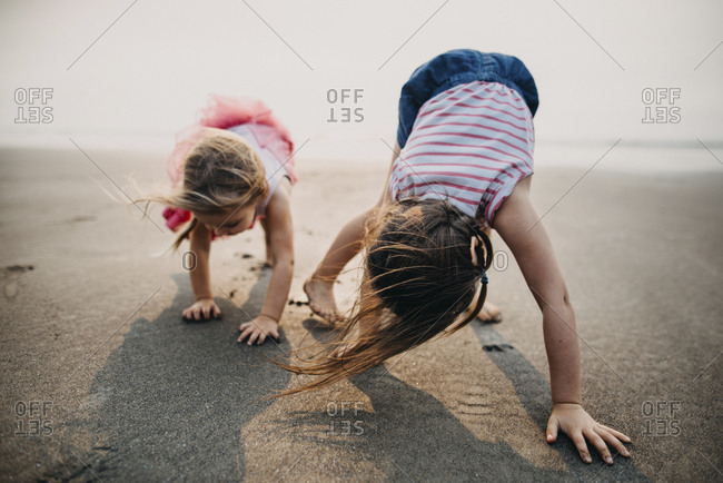 Playful sisters bending on sand at beach against sky