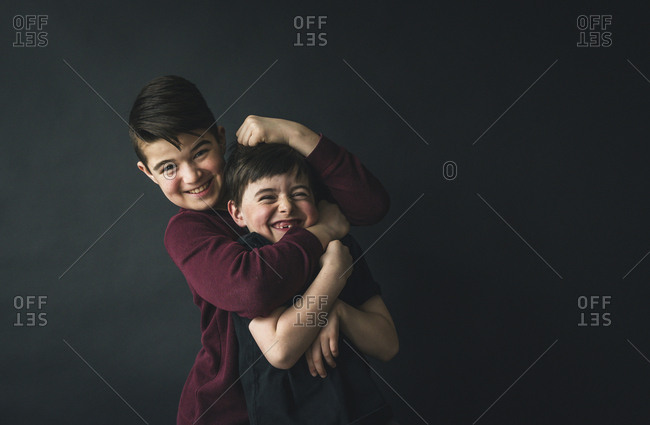 Portrait of happy boy playing with brother while standing against wall