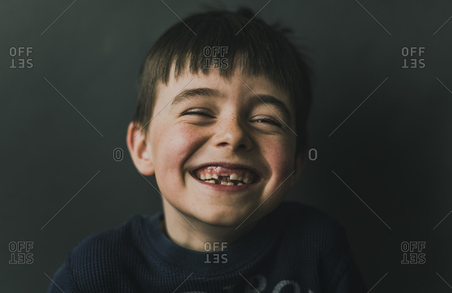Portrait of happy boy standing against wall