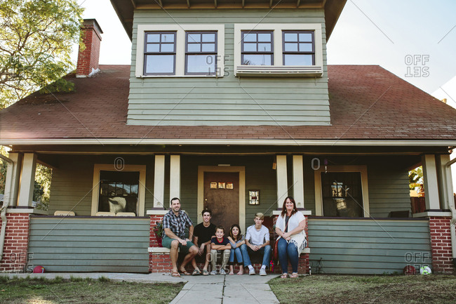 Portrait of happy family sitting by house