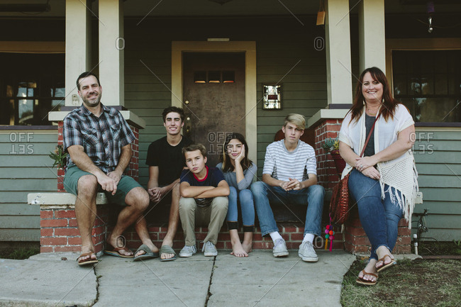 Portrait of happy family sitting on steps by house