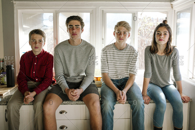 Portrait of siblings sitting on kitchen counter at home