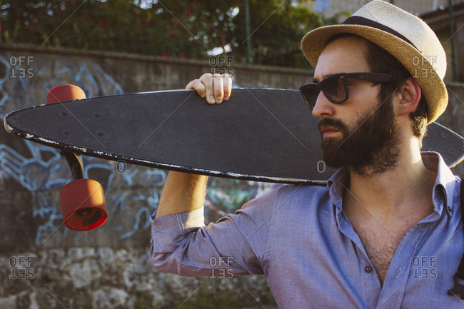 Man wearing sunglasses and hat while holding skateboard against wall