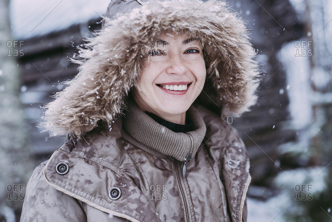 Close-up portrait of happy woman standing outdoors during snowfall