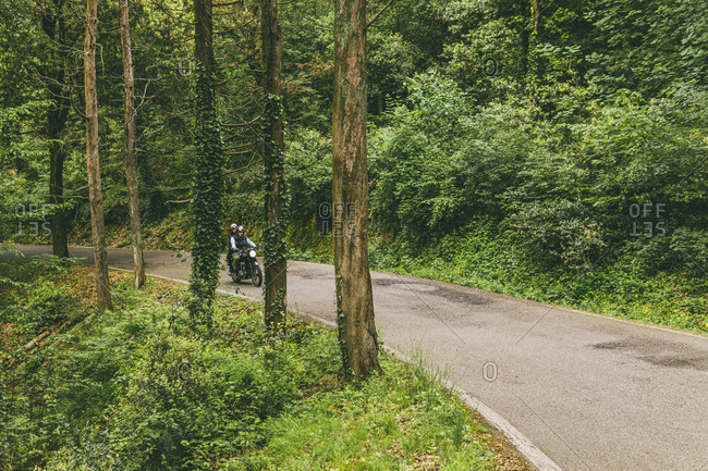 Couple riding motorcycle on road in forest