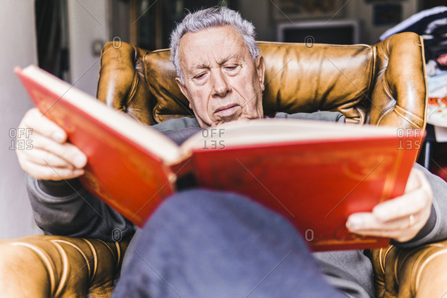 Low angle view of man reading book while relaxing on armchair at home
