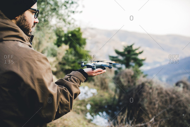 Side view of male hiker holding quadcopter while standing on mountain in forest