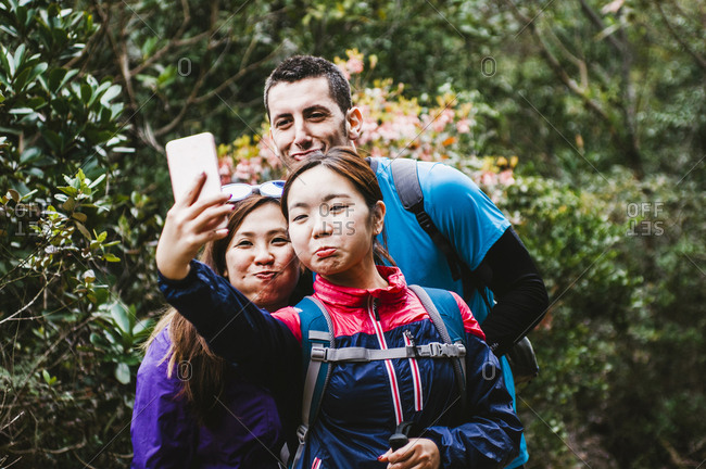 Happy friends taking selfie while standing in forest