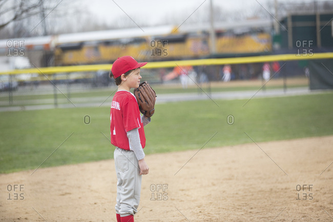 Side view of boy playing baseball at sports field