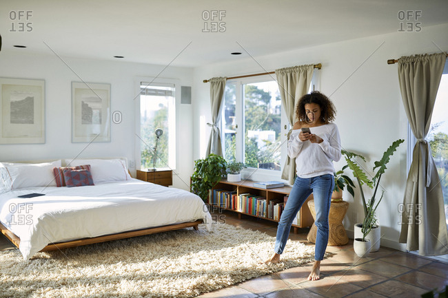 Woman using mobile phone while standing in bedroom at home
