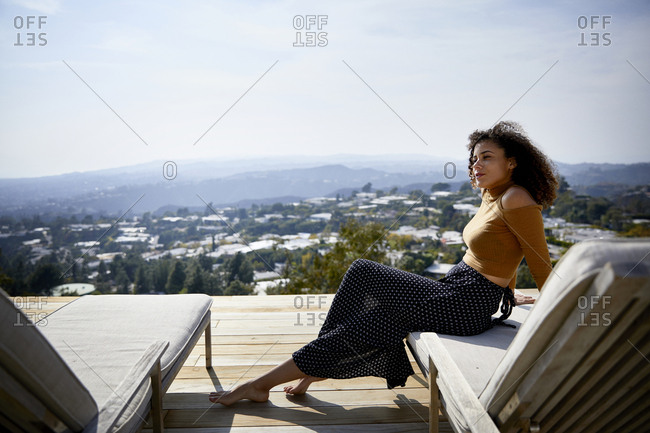 Side view of woman looking away while sitting on deckchair against sky