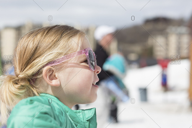 c7dc434fbf6 Side view of girl wearing sunglasses while standing against sky during  winter stock photo - OFFSET