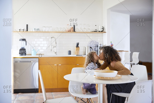 Side view of mother kissing daughter while sitting on chairs at home