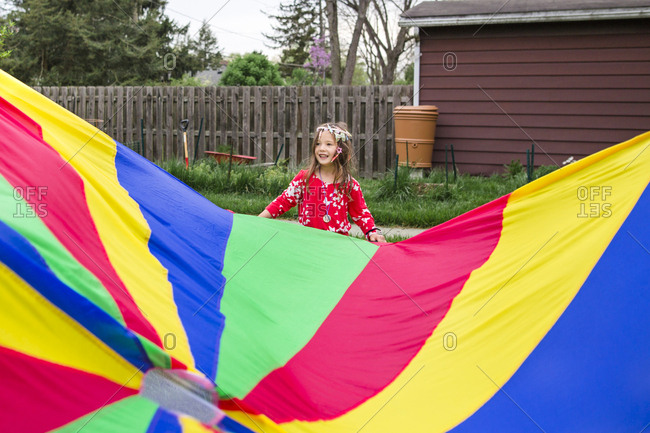 Girl standing by colorful parachute at park