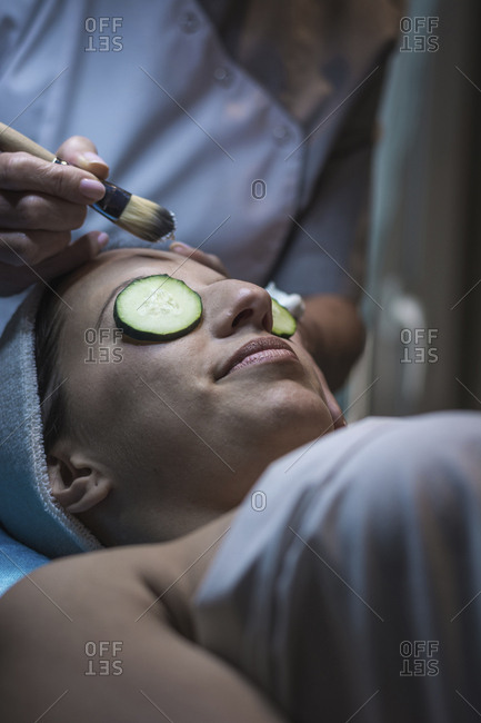 Midsection of beautician applying facial mask to female customer at aesthetic center