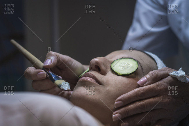 Cropped hands of beautician applying facial mask to female customer at aesthetic center