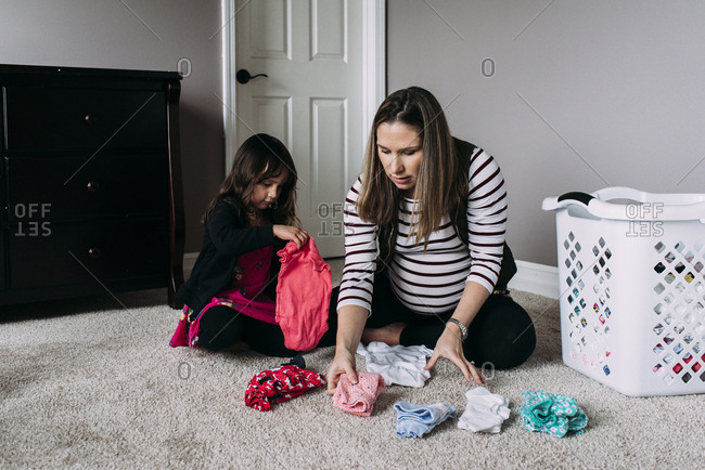 Pregnant mother with daughter folding clothes while sitting on rug at home