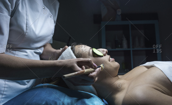 Midsection of beautician applying facial mask to customer at aesthetic center