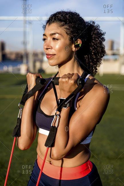 Female athlete exercising with resistance band while standing on grassy field