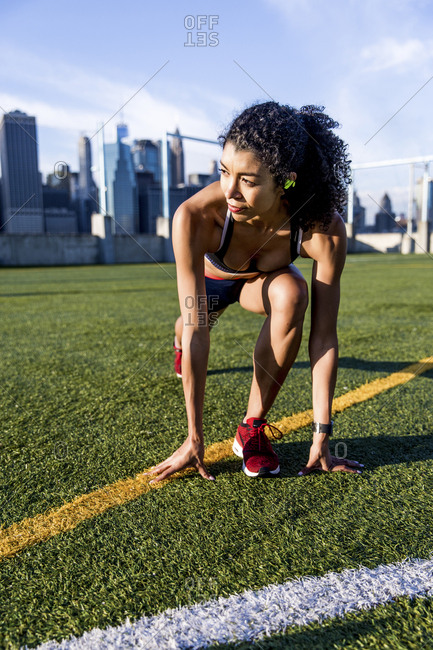 Female athlete looking away while exercising on grassy field against sky