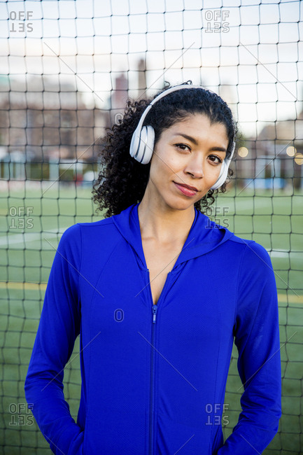 Portrait of confident female athlete listening music while standing by net