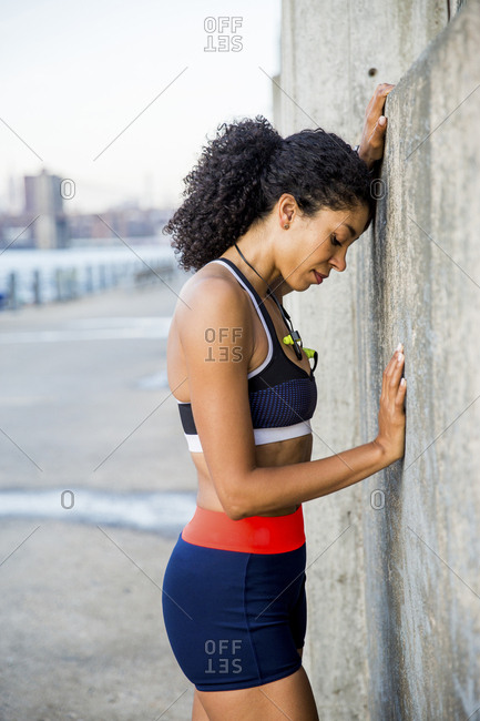 Side view of female athlete with eyes closed leaning on wall against sky
