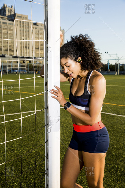 Female athlete leaning on net while standing at playing field against sky
