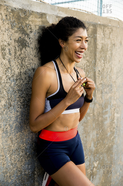 Happy female athlete looking away while standing by wall