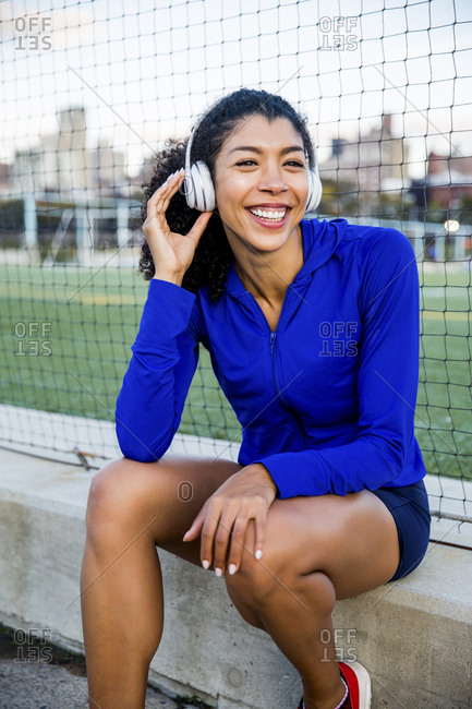 Smiling female athlete looking away while listening music by net