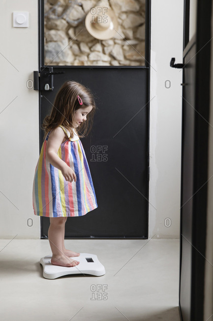 Side view of girl standing on bathroom scale at home
