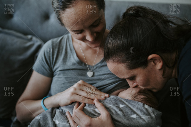 Close-up of lesbian mothers with newborn son sitting on bed at home
