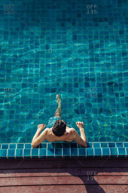 High angle view of shirtless man relaxing in pool at tourist resort