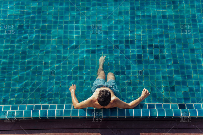 High angle view of shirtless man relaxing while sitting in pool at tourist resort