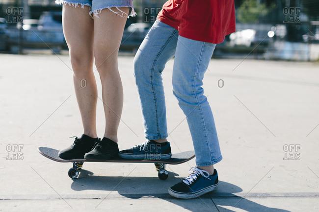 Low section of lesbian couple skateboarding on street