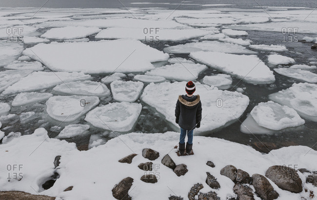 Rear view of boy standing on frozen lake