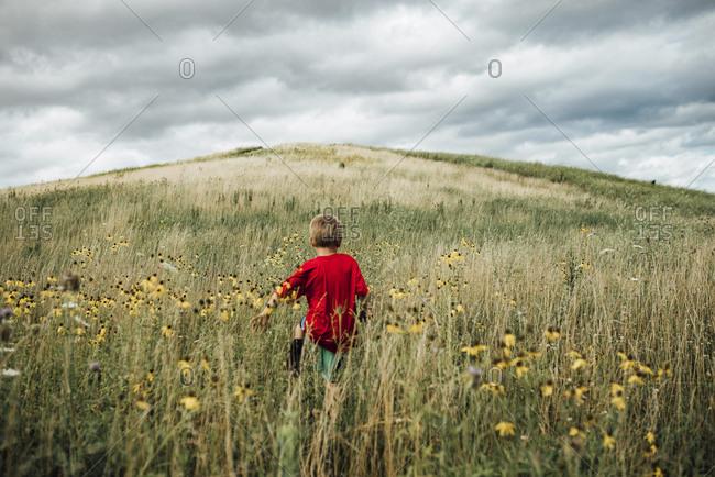 Rear view of boy walking on grassy field against cloudy sky