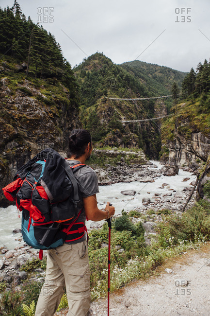 Rear view of male hiker with backpack standing by river against cloudy sky at Sagarmatha National Park