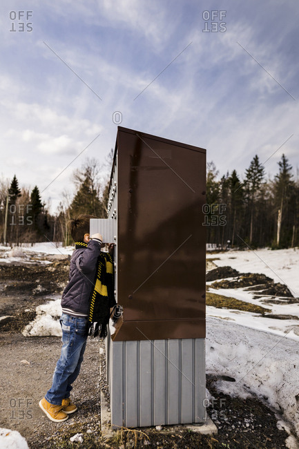 Side view of boy looking into public mailboxes while standing against sky during winter
