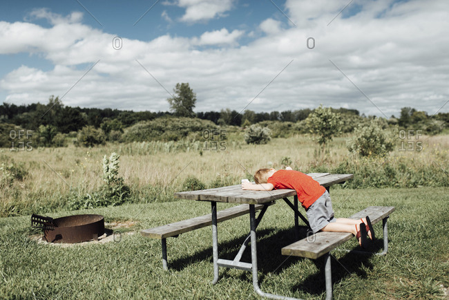 Side view of boy lying on picnic bench against cloudy sky during sunny day