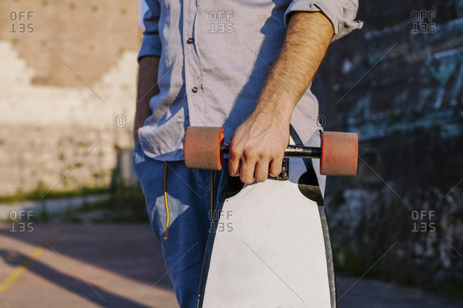 Midsection of man holding skateboard while standing against wall during sunset