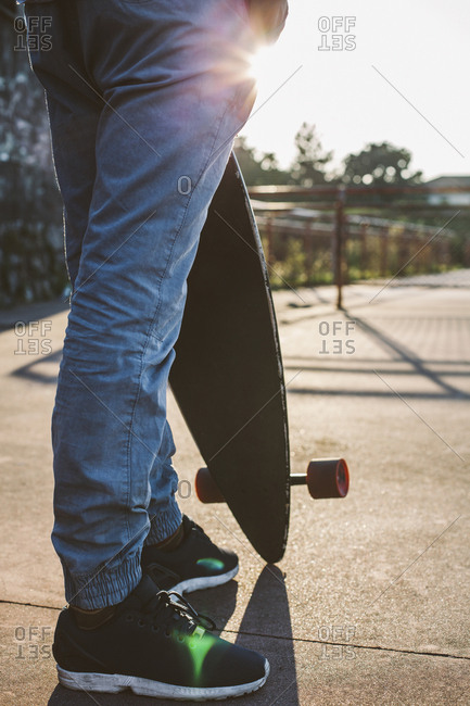 Low section of man holding skateboard while standing against sky during sunset