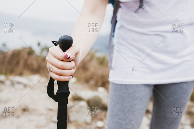 Midsection of female hiker holding hiking pole while standing on mountain