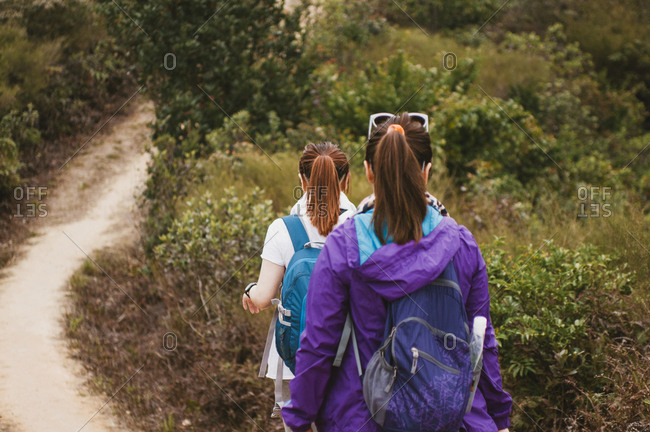 Rear view of female hikers with backpacks walking on dirt road amidst plants
